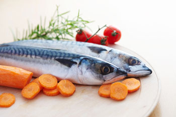 Two mackerels on a board with carrots
