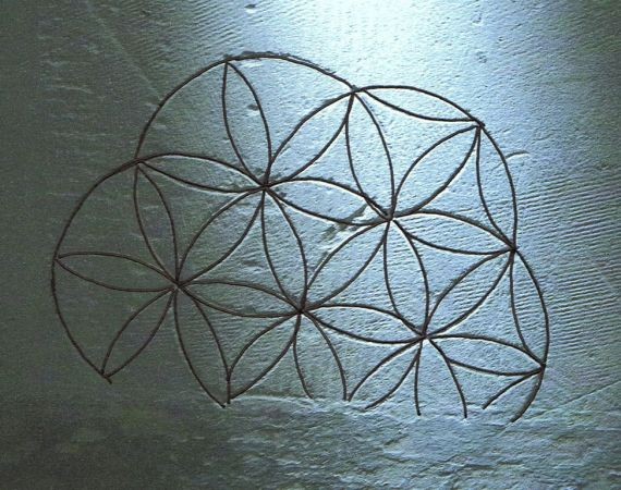 Multiple daisy wheel copy – A complex compass drawn symbol from All Saints church,  Litcham. Such designs are aongst the most common types of graffiti recorded by the survey  and are believed to have functioned as ritual protection markings – designed to ward off the  'evil eye'. Photo courtesy Norfolk Medieval Graffiti Survey