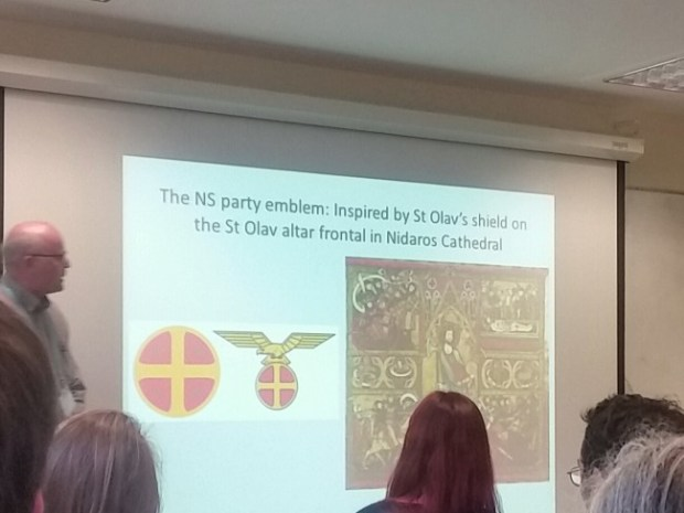 Øystein Ekroll showing a slide from his talk about the NS party and the use of St. Olav's shield as the party's emblem. Photo by Medievalists.net