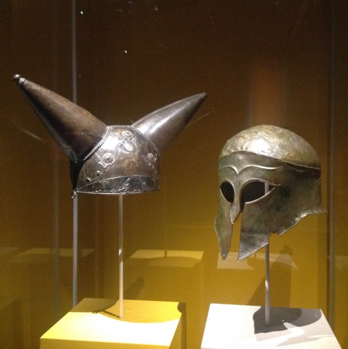 (L) Horned helmet. Bronze, glass, Found along the Thames river near Waterloo, London, England (200-100 BC). (R) Greek helmet, bronze. Olympia, South-Western Greece (460 BC). The British Museum. Photo by Medievalists.net