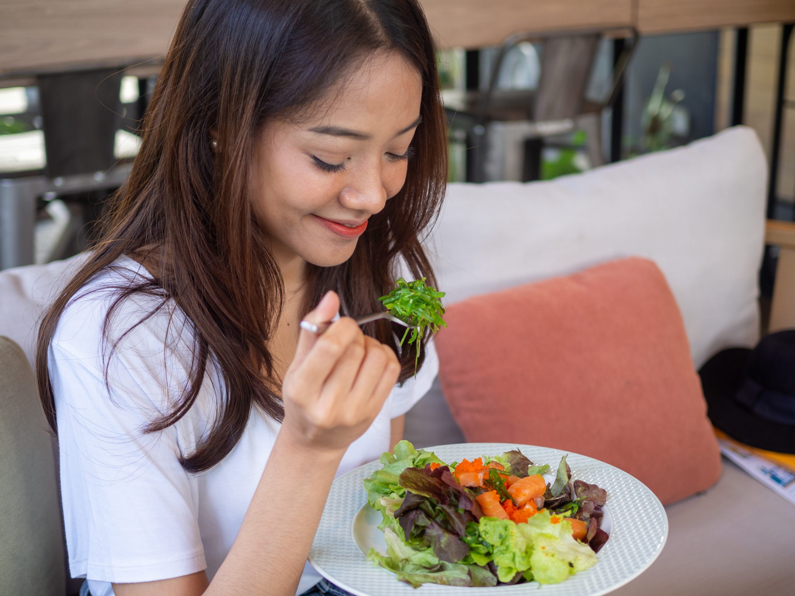 Asian women are happy to eat salmon salad. Food for good health. MEDIjobs