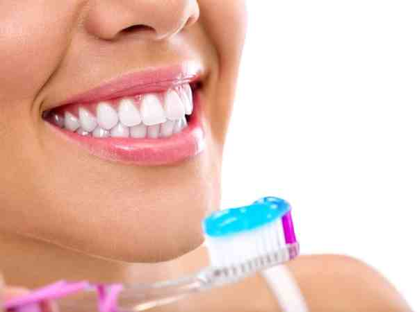 Smiling young woman with healthy teeth holding a tooth-brush