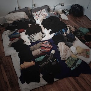 Our bed piled with clothing