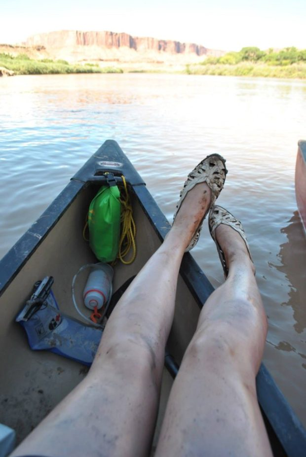 my legs resting over the side of the canoe on the Green River, Utah