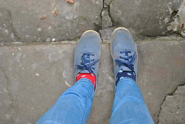 one red and one blue polka dot sock in my keds sneakers