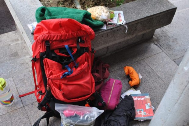 my red backpack with guidebooks, toiletries bags popcorn and waterbottle spread out on the ground