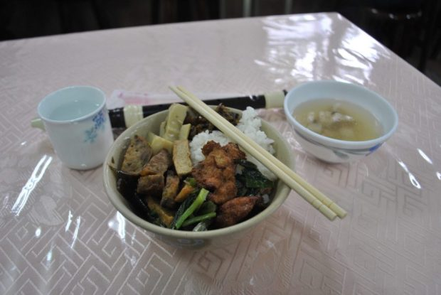 a bowl filled with tofu, vegetables and rice beside a bowl of broth and a cup of hot water