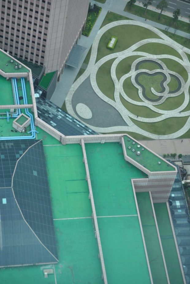 the view from the 89th floor of Taipei 101 down onto rooftops and a garden constructed like a large flower