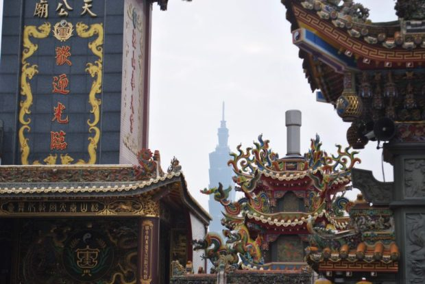 Taipei 101 in the background, ornate roofs of religious temples in the foreground