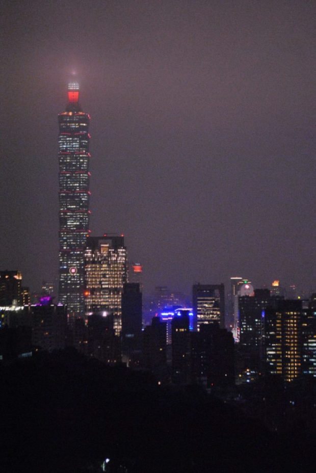 The lights of Taipei 101 and other tall buildings shine in the foggy night