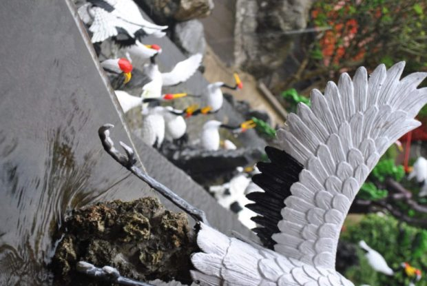 plastic white and black cranes decorate a terraced fountain at the monastery at Lion's Head Mountain Shihtoushan