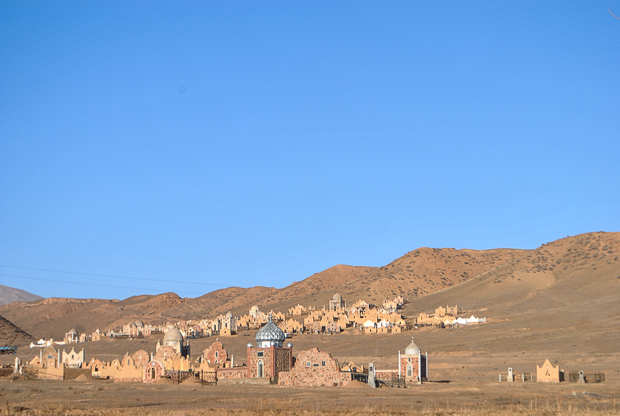 blue sky and a brown hill with a large cluster of kyrgyz mausoleums