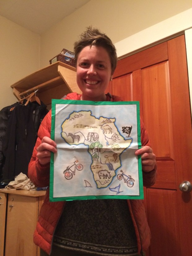 me holding up a handmade card with africa drawn on it with animals pirate flag and our bicycles
