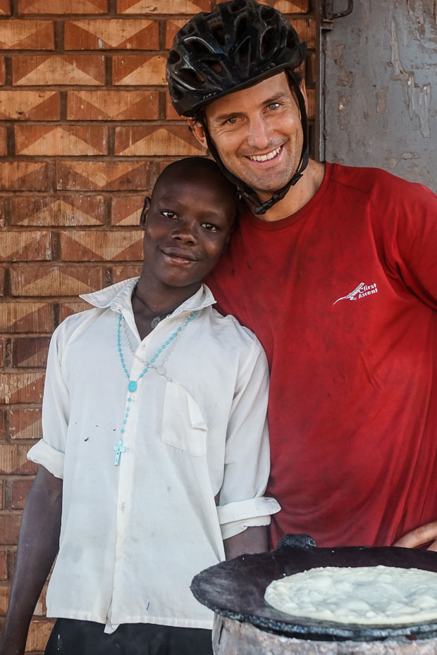 evan poses with a young boy in a white shirt and a blue rosary necklace in front of a skillet with a bubbling chapati in uganda