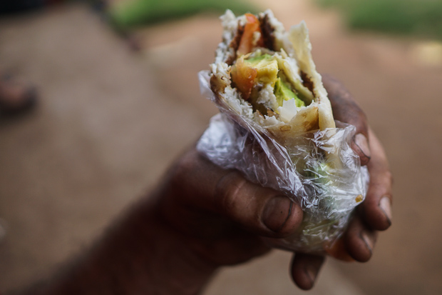 evans dirty hand holding a half eaten rolex, a ugandan omelette wrap with tomatoes onions and avocado