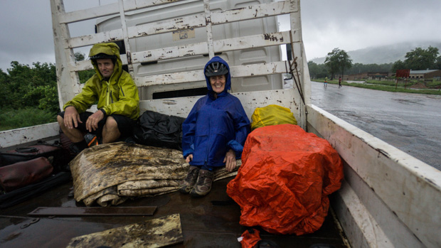 Anne and Evan in wet rain jackets with panniers sit in the back of a truck leaving Chirundu Border, Zimbabwe