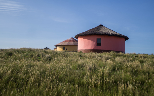 a pink round house or rondavel in the tall grass in the Transkei near what's called the Wild Coast by the tourism industry