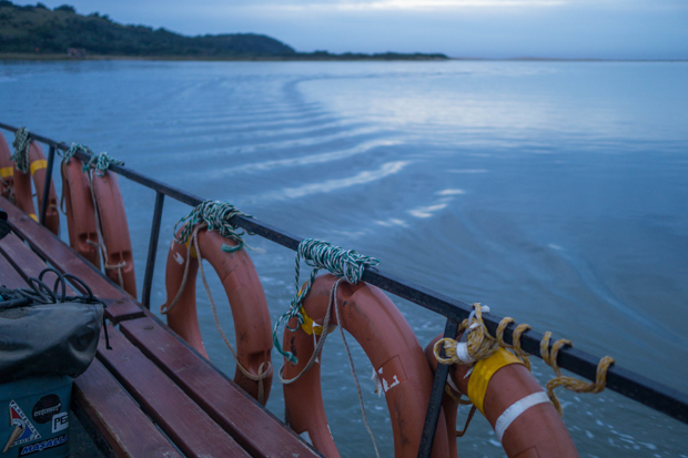 calm dusk water on the Kei River, picture taken from the ferry with a rail of life rings