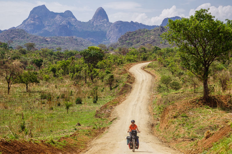 me riding along a dirt road in northern Uganda with the mountains of South Sudan in the background