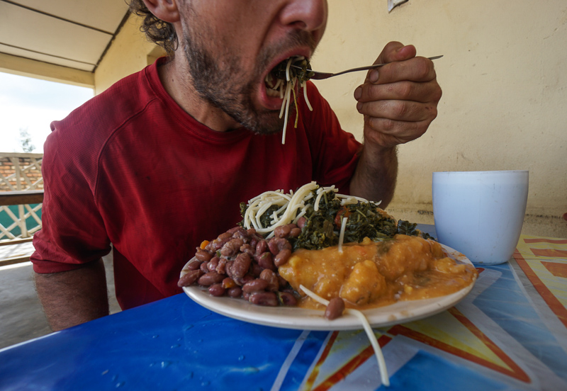 evan eating a big mouthful of spaghetti from a plate piled high at a rwandan buffet