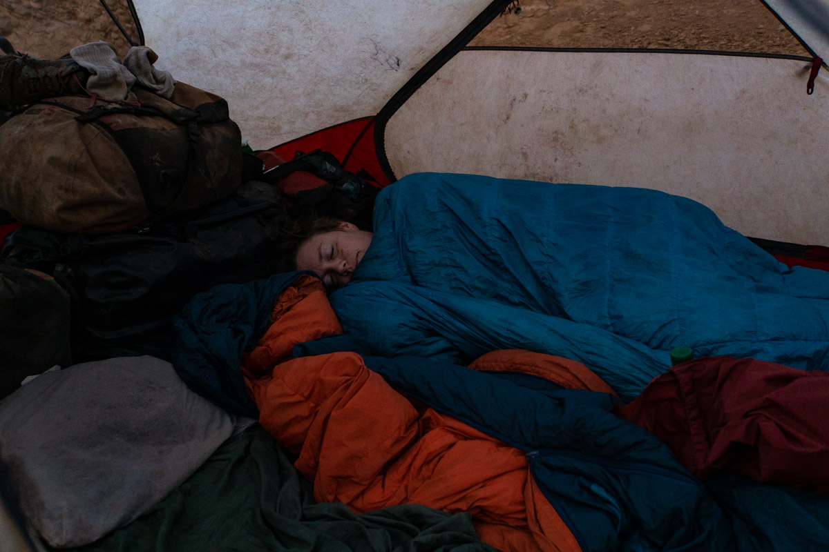 snuggling with two sleeping bags in our tent in the anti atlas mountains of morocco while bicycle travelling