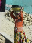 Women carry the sand and gravel