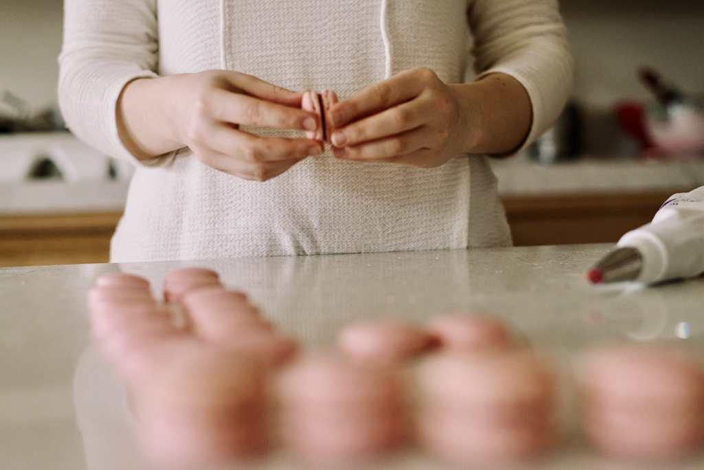 Pâtissière en train de monter un macaron rose