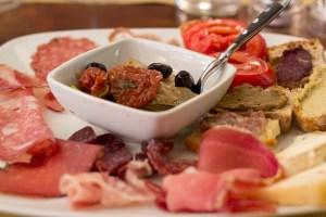 托斯卡纳混合前菜(Antipasto toscano),包括冷切片肉、腌菜和配了不同酱的面包