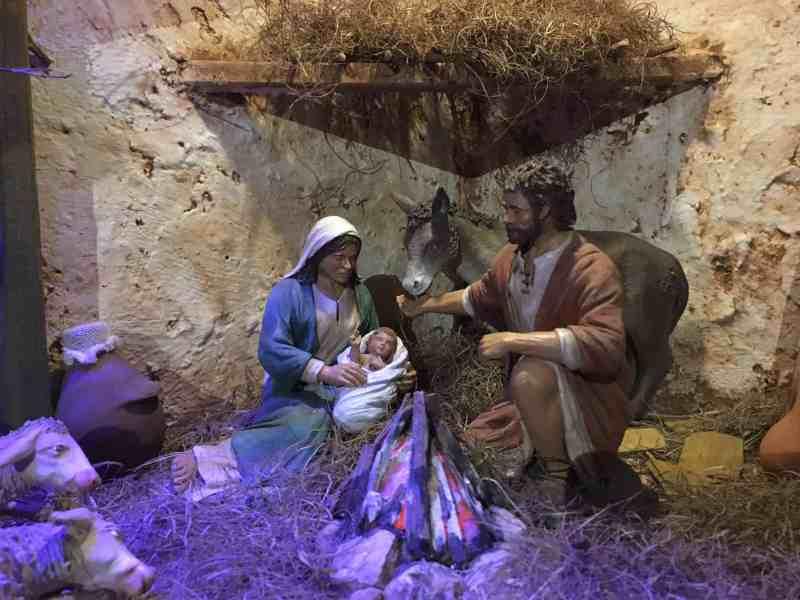 Josef lenkt den warmen Atem des Esels aufs Jesuskind