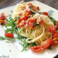 Leckere Pasta auf Rucola mit Tomaten und Knoblauch in Olivenöl gedünstet