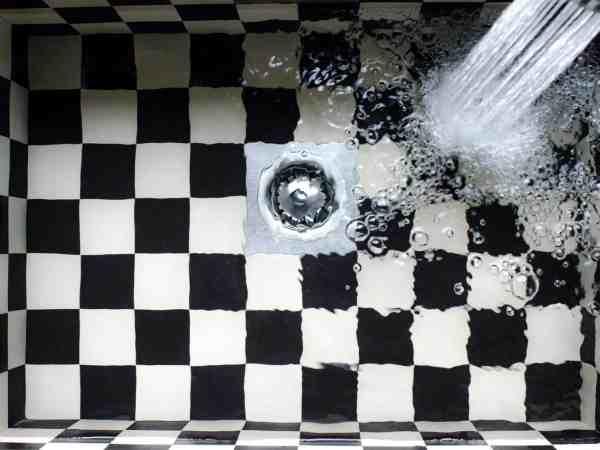 Waschbecken mit Wasser und Schachbrettmuster