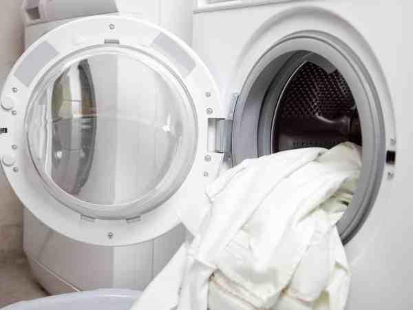 weiße Wäsche hängt aus offener Maschine