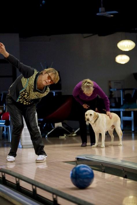Mona er svagtseende og er sammen med vennerne til bowling. Hendes førerhund Folmer kigger på mens hun sender kuglen afsted mod keglerne.