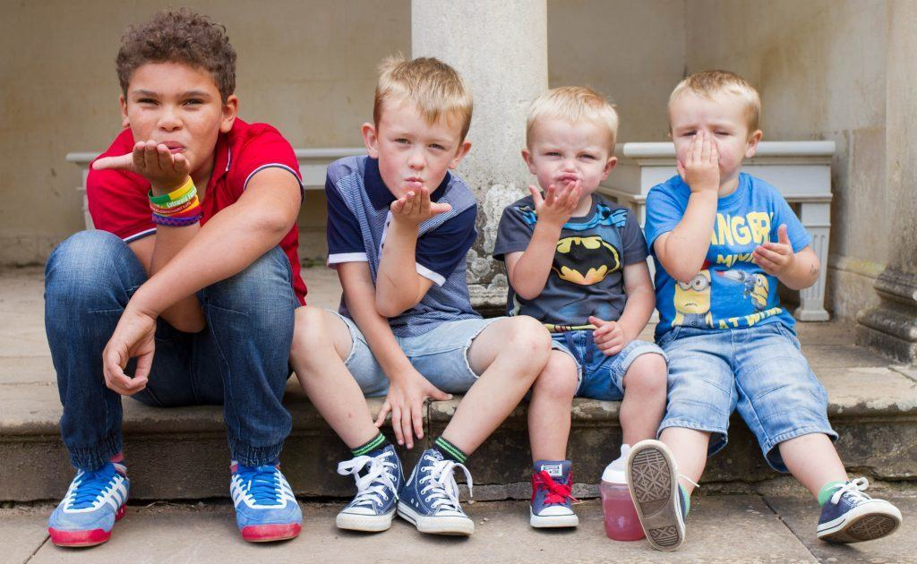 Four children sat on a step during a photoshoot blowing kisses to the camera