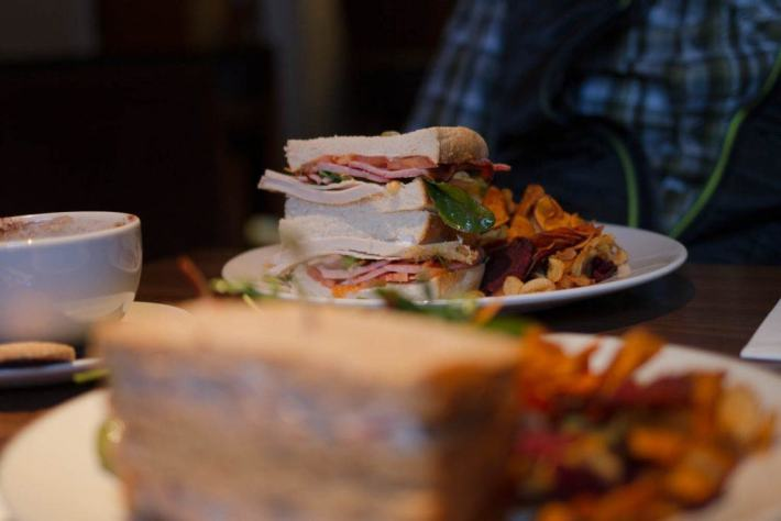New Lanark Mill Hotel, Review. Photo of a sandwich with lots of meat filling and vegetable crisps on the side of the plate
