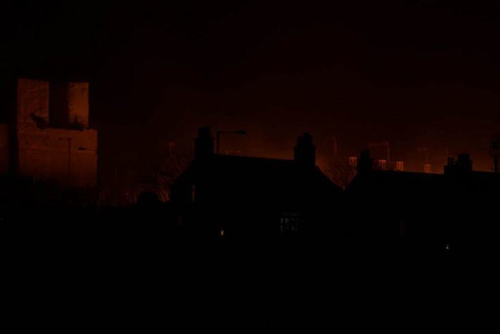 Photo of the silhouettes of house and an orange glow from the torches