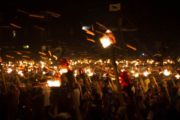 Shetland, Up Helly Aa. Photo of a torch lit procession. Sparks are flying in the wind