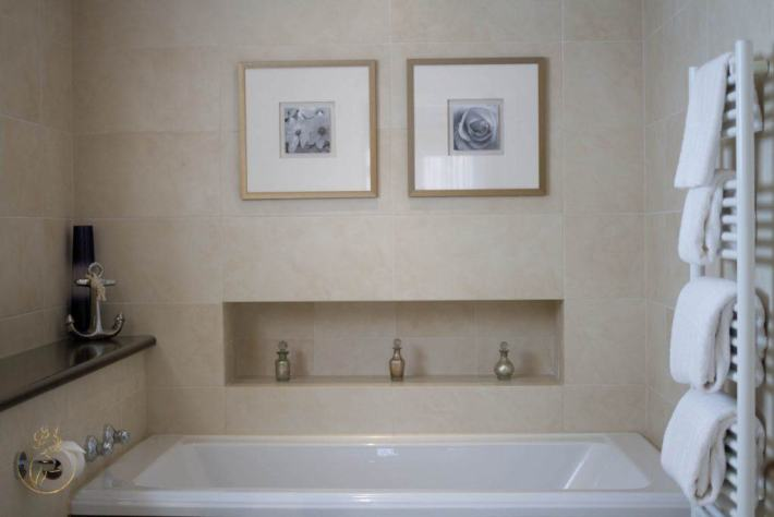Photo of a bathroom. Bath across the width of the room, large tiles throughout. A towel rail on the right with towels on.