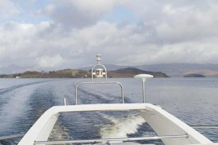 Photo of: Celtic Warrior boat on Loch Lomond. Looking out to the back of the boat and some of the islands