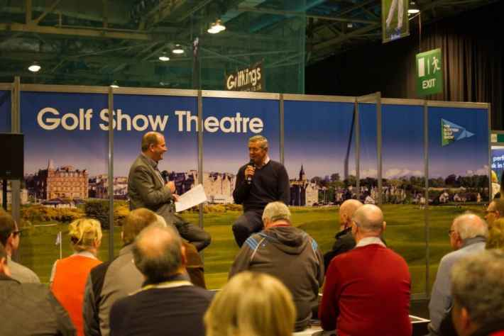 Photo of two men on a small stage doing a Q&A about golf in front of an audience
