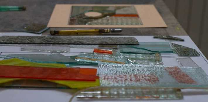 Photo of pieces of glass on a table ready to be used to make a small stained glass window.