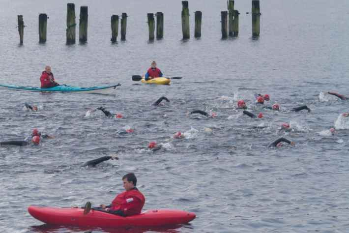 Great Scottish Swim, Loch Lomond. Photo of people swimming in the water - only caps and arms visible in the water. People in safety kayaks watching
