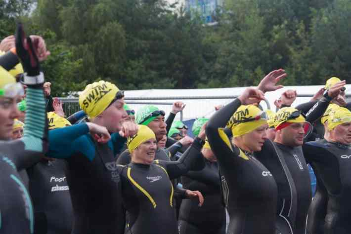 Loch Lomond, Great Scottish Swim. Group of people in wetsuits, warming up their arms for the swimming event