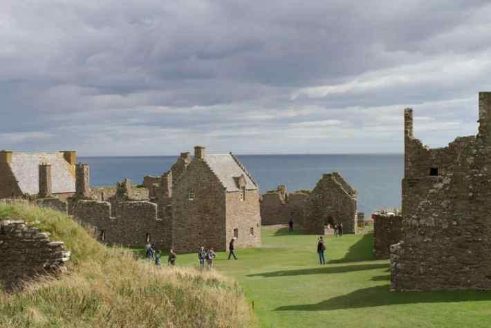 Dunnottar Castle, Aberdeenshire. Stone buildings - some ruins. People walking over the grass.
