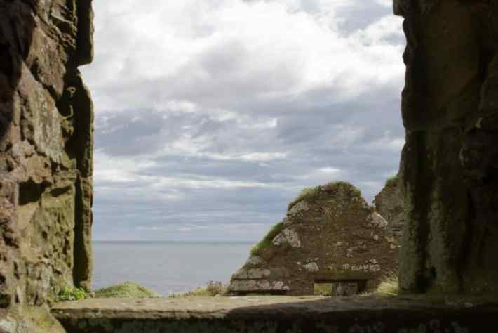 Dunnottar Castle, Aberdeenshire. photo of clouds and the sea through the window of the castle ruins