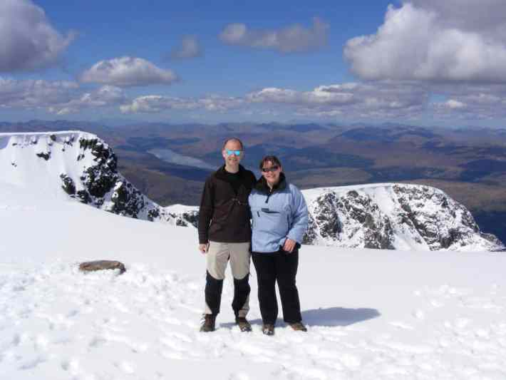 Two people standing on top of Ben Nevis. Snow on the ground and a view of the mountains in the background