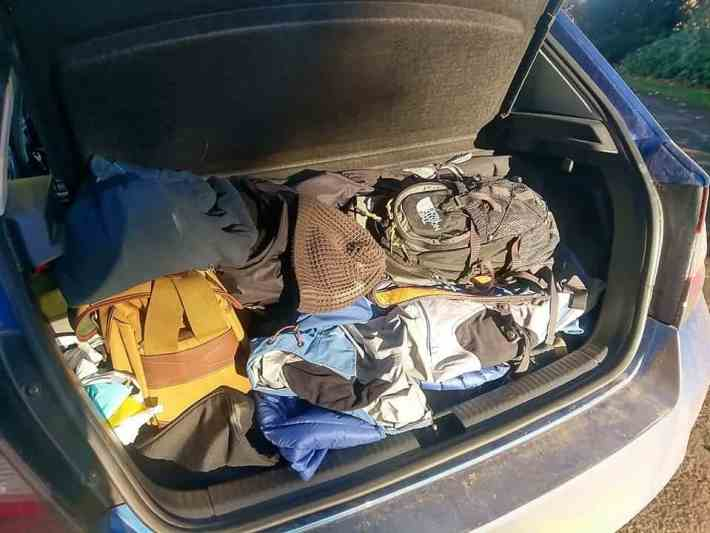 Car boot full of bags and winter coats for a road trip