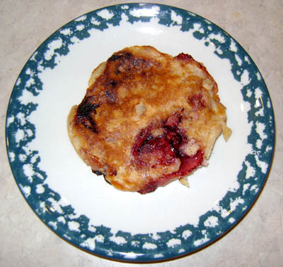 closeup of a strawberry pancake with a large strawberry piece showing through!