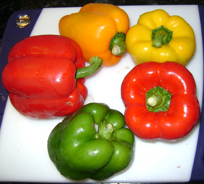 colorful red yellow and orange bell peppers, ready to be sliced