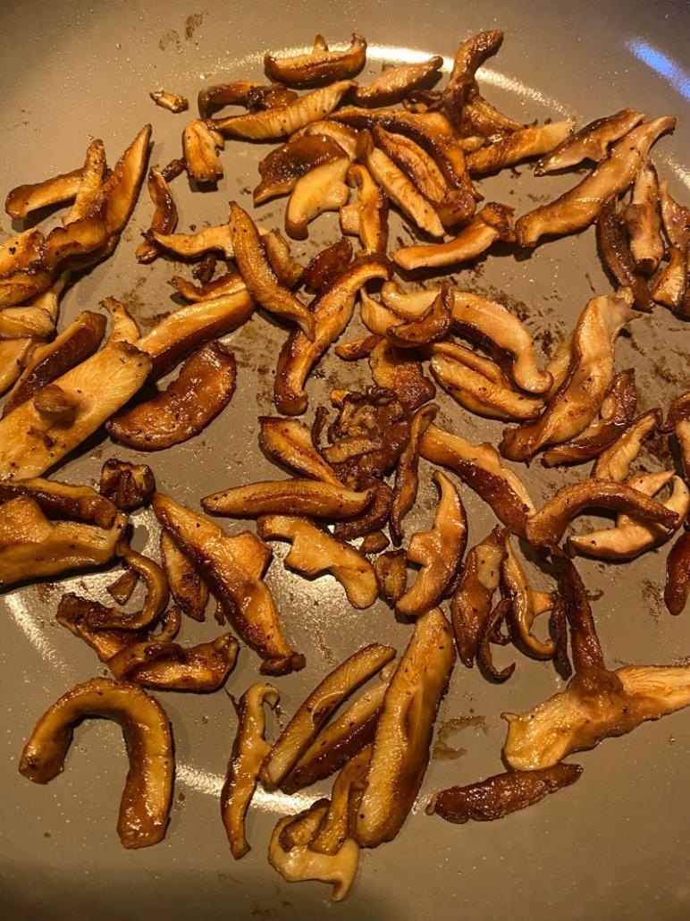 shiitake mushrooms cooking on a frying pan